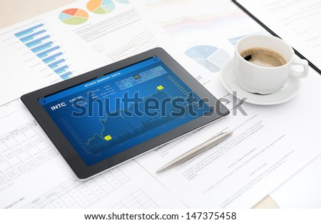 Modern digital tablet with stock market data application on the screen lying on a desk with some papers and documents, pen and a cup of coffee.