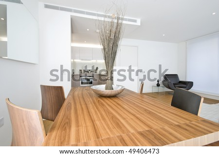 Modern dining area with wooden table, designer chairs and kitchen in a backround - stock photo