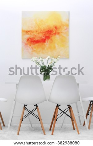 Modern dining room. White chairs and table with bouquet of flowers, abstract bright picture on the wall - stock photo