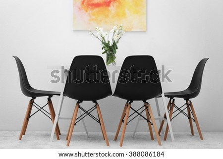 Modern dining room. White table with bouquet of flowers and black chairs, abstract bright picture on the wall - stock photo
