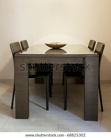 Modern dining room with brown chairs and a table with glass coating
