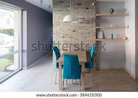 Modern dining room with wooden table, turquoise leather chairs, old grey brick wall and shelves