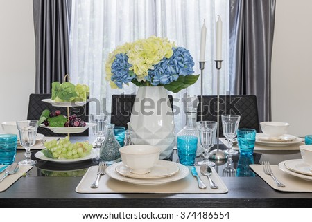 modern dinning room with table set on glass table and vase of flower
