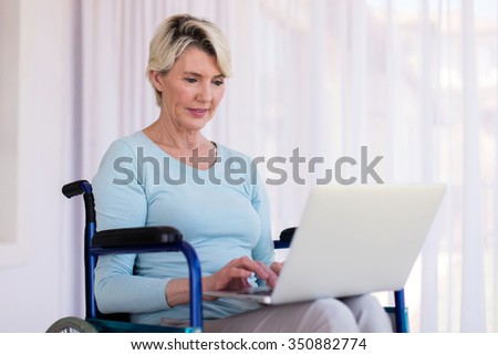 modern disabled middle aged woman using laptop - stock photo
