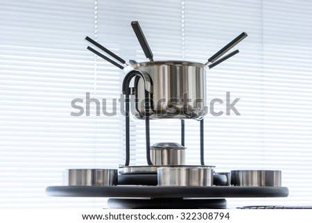 modern dishware, fondue set on window background  - stock photo