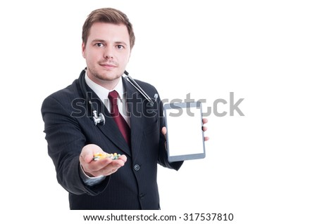 Modern doctor holding pills and white blank tablet screen with copy space - stock photo