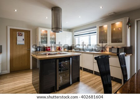 Modern Domestic Kitchen / A modern domestic kitchen with high gloss units, rounded corners and an island - stock photo
