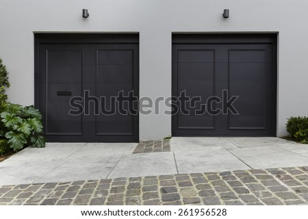 Modern Driveway and Dark Garage Doors - stock photo