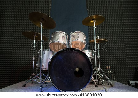 Modern drum set on black stage background prepared for playing. Professional drum kit with some cymbals on stage before a live concert. Drummer, music band, night show, sound recording concept - stock photo