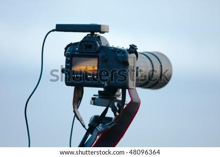 Modern DSLR camera with telephoto lens against soft blue sky - stock photo