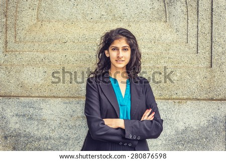 Modern East Indian American Student. Dressing in black blazer, blue under shirt, crossing arms,  a young girl with long curly hair standing by wall, smiling, looking at you. Instagram filtered effect. - stock photo