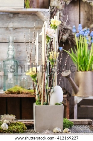 Modern easter decoration with carnations, catkins and eggs.