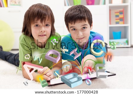 Modern education and online learning possibilities - boys using tablet computer - stock photo