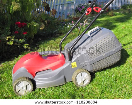 Modern electric lawn mower on the mown down lawn