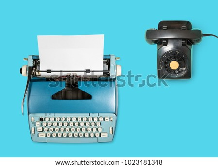 Modern electric typewriter and rotary dial phone on plain background with copy space