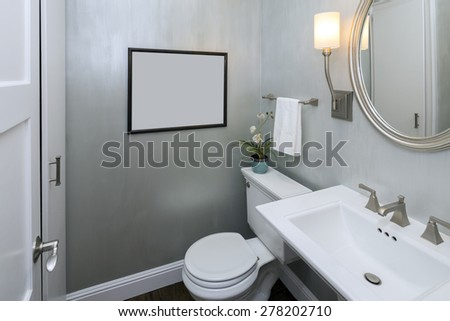 Modern elegant bathroom in sophisticated silver with withe appliances, round framed mirror  and art frame for copy space. - stock photo