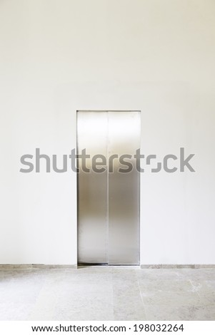 Modern elevator with closed doors extreme closeup detail of a lift in works - stock photo