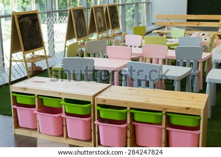 Modern empty kindergarten chairs and desks with chalkboards - stock photo