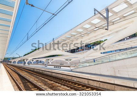 Modern empty railway station with transparent ceiling with blue sky on a background