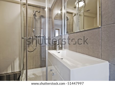 modern en-suite bathroom with shower cabin and box shape sink - stock photo