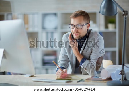Modern engineer speaking on cellphone at workplace - stock photo
