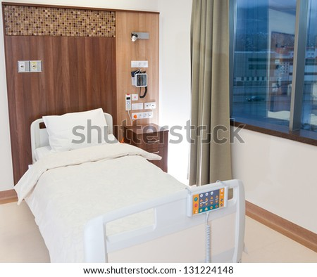 Modern equipped and comfortable empty bed in hospital room - stock photo