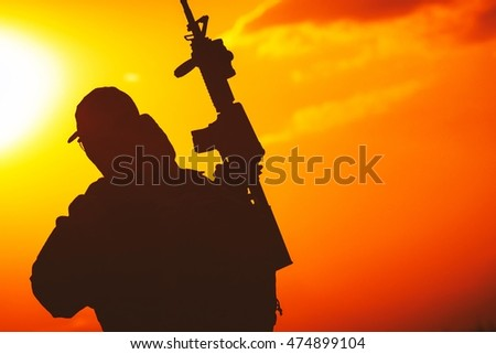 Modern Equipped Soldier with Rifle Sunset Silhouette. Military Concept