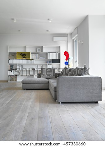 modern fabric sofa in the modern living room with wooden floor and white bookcase - stock photo
