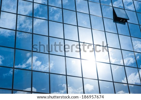 Modern facade of glass and steel with open window reflecting sky and clouds. - stock photo