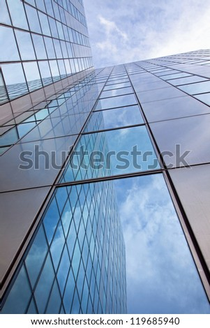 modern facade of glass and steel with reflections of the blue sky - stock photo