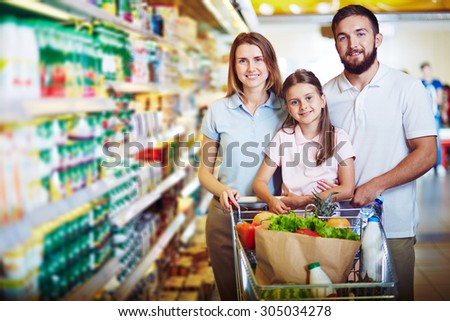 Modern family looking at camera while buying food in supermarket - stock photo