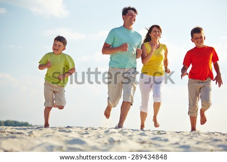 Modern family of four running on sandy beach - stock photo