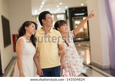 Modern family standing in the mall, the daughter pointing at something with smile