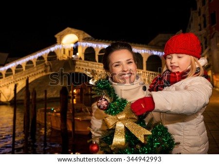 Modern family take the best of Christmas season by having a fascinating trip to Venice, Italy. Happy mother and daughter with Christmas tree in the front of Rialto Bridge