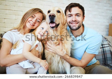 Modern family with dog looking at camera during home rest