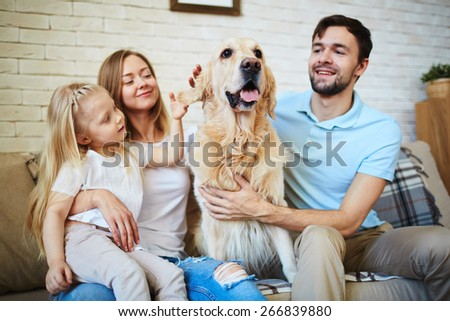 Modern family with pet resting on sofa at home - stock photo