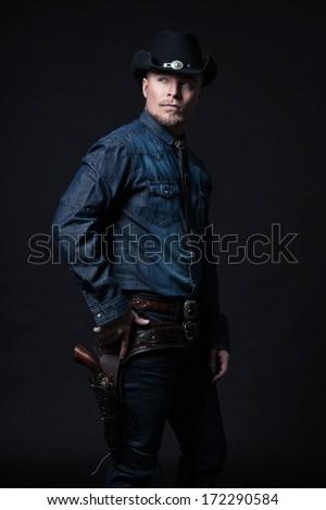 Modern fashion cowboy. Wearing black hat and blue jeans shirt. Pulling his gun. Blonde hair and beard. Studio shot against black. - stock photo