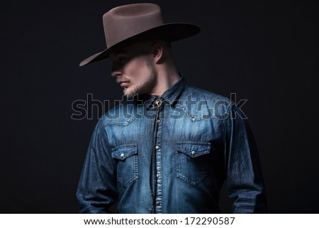 Modern fashion cowboy. Wearing brown hat and blue jeans shirt. Blonde hair and beard. Studio shot against black.