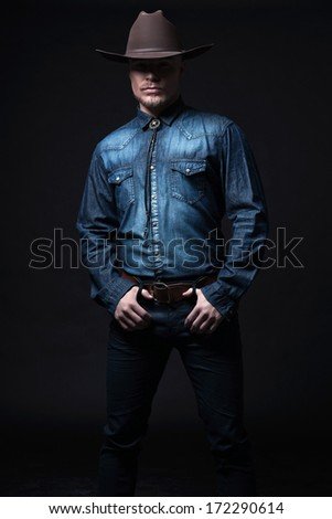 Modern fashion cowboy. Wearing brown hat and blue jeans shirt. Blonde hair and beard. Studio shot against black. - stock photo