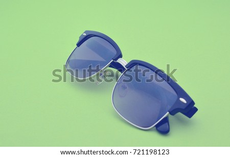 Modern fashion glasses close-up on a colored green background. Protect your eyes from sunlight.