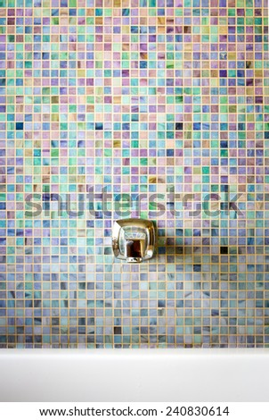 Modern faucet against a mosaic glass tile wall - stock photo