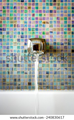 Modern faucet against a mosaic glass tile wall with running water