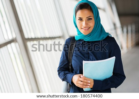 modern female middle eastern college student holding a book - stock photo