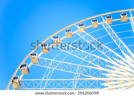 Modern ferris wheel with blue sky on the background. - stock photo