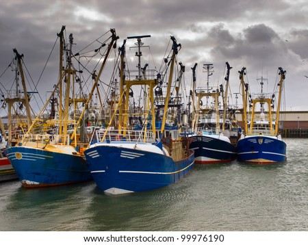 Modern fishing boats under a brooding sky in a dutch fishing harbor - stock photo