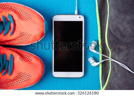 Modern fitness and gym workout concept. Healthy lifestyle background with blank copy space smartphone screen, earphones and sport training shoes close up. - stock photo