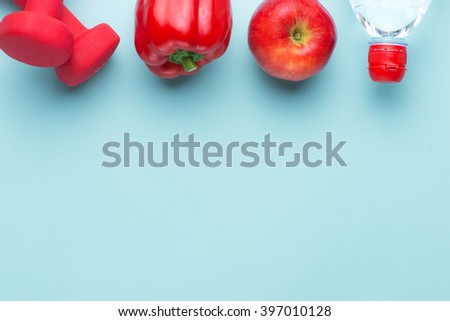 Modern fitness healthy sport gym woman with copy space. Top view angle. Dumbbells, red apple, bell pepper and water bottle close up together for diet concept.  - stock photo