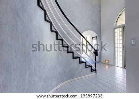 Modern foyer with high ceiling and tile floor. View of steep staircase with black and white railings