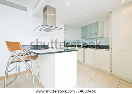 Modern fully fitted kitchen in vanilla white with breakfast bar and orange chairs - stock photo