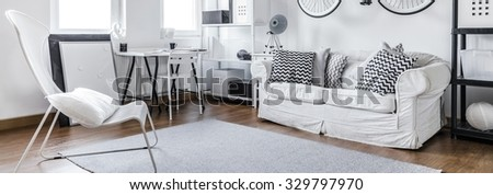 Modern furniture in black and white studio flat - stock photo